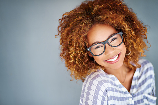 Young woman smiling with glasses and a grey background
